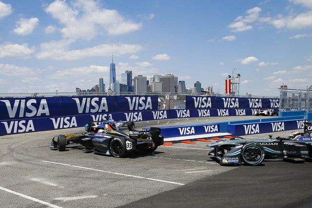 Formula E Racers taking a tight corner with downtown New York City in the background